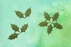 Folhas do azevinho no papel feito a mão Imagens de Stock