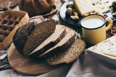 Folhas do pão que encontram-se no fundo bege com um copo à moda amarelo do leite e um prato preto do queijo com furos e Fotos de Stock Royalty Free