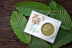 Folhas do speciosa ou do kratom de Mitragyna com os produtos medicinais nos comprimidos, nas cápsulas e no pó na bacia cerâmica b imagem de stock royalty free