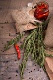Folhas dos alecrins e pimentões vermelhos em um frasco de vidro Pimenta preta e vermelha em um fundo da tabela Produtos orgânicos Fotos de Stock Royalty Free
