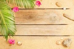 Folhas e areia da palmeira no fundo de madeira - praia Fotografia de Stock Royalty Free