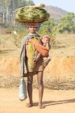 Folhas e bebê tribais do carryng da mulher de Orissan Imagens de Stock