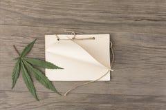 Folhas e flores do cânhamo com o caderno feito a mão do ofício no fundo de madeira do grunge velho Vista superior Modelo de Minim fotos de stock royalty free