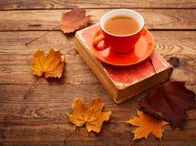 Folhas, livro e copo de outono do chá na tabela de madeira Fotografia de Stock Royalty Free