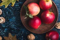 Folhas, maçãs e nozes de outono na placa azul Imagens de Stock Royalty Free
