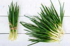 Folhas novas das penas de uma cebola verde em um fundo de madeira branco, recolhidas em um pacote e dispersadas Imagem de Stock Royalty Free
