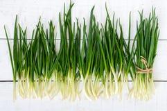 Folhas novas das penas de uma cebola verde em um fundo de madeira branco, recolhidas em um pacote e dispersadas Foto de Stock