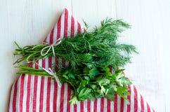 Folhas verdes da salsa e do aneto no guardanapo de linho natural no fundo de madeira Fotografia de Stock