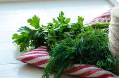Folhas verdes da salsa e do aneto no guardanapo de linho natural no fundo de madeira Fotos de Stock