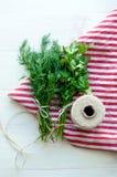 Folhas verdes da salsa e do aneto no guardanapo de linho natural no fundo de madeira Imagem de Stock