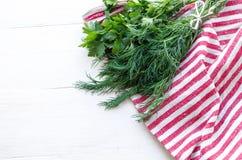 Folhas verdes da salsa e do aneto no guardanapo de linho natural no fundo de madeira Foto de Stock Royalty Free