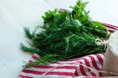 Folhas verdes da salsa e do aneto no guardanapo de linho natural no fundo de madeira Foto de Stock