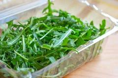 Folhas verdes saudáveis frescas da rúcula no recipiente plástico no fundo de madeira claro imagens de stock