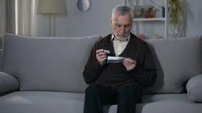 Folheto da leitura do ancião com instruções para a medicamentação, auto-tratamento arriscado filme
