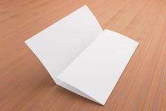 Folheto dobrável em três partes vazio no fundo de madeira Foto de Stock
