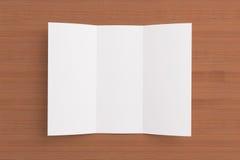 Folheto dobrável em três partes vazio no fundo de madeira Fotografia de Stock Royalty Free
