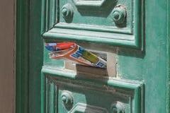 Folheto que cola fora da caixa postal do entalhe da letra da porta da rua foto de stock royalty free