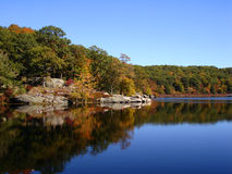 Foliage in Harrimen State Park. Forest reflects in waters of small lake. Small pond in Harriman state park, NY. Hikers rest after long hike. Fall forest reflects stock photos