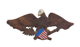 Folk art wooden bald eagle isolated. Old hand carved folk art wooden bald eagle, holding a red, white, and blue shield.  Isolated on white Royalty Free Stock Image
