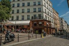 Folk, byggnader och blå himmel på gatan av Montmartre på Paris Royaltyfri Fotografi