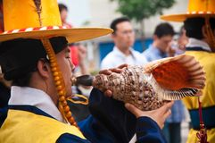 Folk celebrations in Seoul, yellow dressed guard playing on a shell Royalty Free Stock Photography