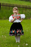 Folk costumes little girl on the meadow stock photos