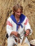 Folk crafts.The Fourth International Historical Festival. Folk crafts. A man making wooden spoons with the help of an axe.The Fourth International Historical Stock Photo