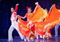 Folk Dance: Orange female and partner Stock Photography