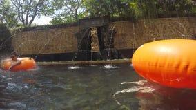 Folk för blandat lopp som kopplar av och har gyckel i Aquapark Simbassäng för flod för unge- och vuxen människarör lat i Waterpar stock video