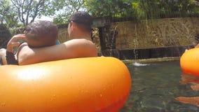 Folk för blandat lopp som kopplar av och har gyckel i Aquapark Simbassäng för flod för unge- och vuxen människarör lat i Waterpar lager videofilmer