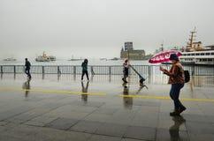 Folk för Istanbul ångbåtpir som går i regnet Royaltyfri Bild