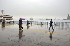 Folk för Istanbul ångbåtpir som går i regnet Royaltyfria Bilder