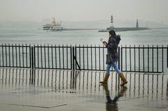 Folk för Istanbul ångbåtpir som går i regnet Royaltyfria Foton