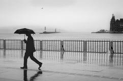 Folk för Istanbul ångbåtpir som går i regnet Arkivbilder