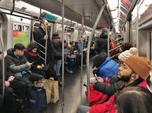Folk för pendlare för NYC-gångtunneldrev som rider gångtunnelbilen för att arbeta fullsatt stadsdrevMTA arkivfoton