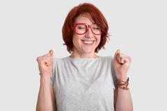 Folk framgång, berömbegrepp Den extatiska röda haired kvinnan med kort hår, tagnävar, har det mjuka leendet, påklädd arkivbild