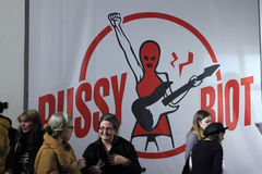 Folk framme av den enorma affischen av Pussytumulten Royaltyfri Fotografi