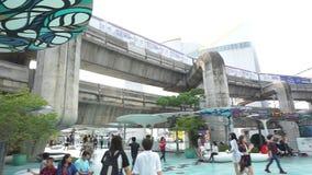folk framme av den Siam Paragon shoppinggallerian med BTS-skytrain i bakgrund arkivfilmer