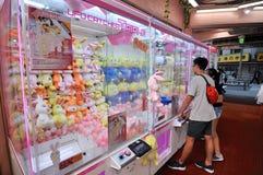 Folk framme av en japanska Toy Crane Vending Machine i Tokyo royaltyfri foto