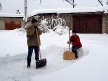 Folk fri bort snöskyfflarna efter tungt snöfall fotografering för bildbyråer