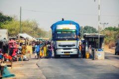 Folk gatuförsäljare som säljer gods till att passera trafik arkivfoto
