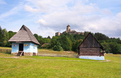 A folk houses and castle in Stara Lubovna. A summer view of authentic, centuries old, folk houses located in the open-air museum (skansen) of Stara Lubovna, Spis royalty free stock images