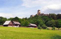 Folk houses and castle in Stara Lubovna. A summertime view of authentic, centuries old folk houses located in the open-air museum of Stara Lubovna, Spis region stock image