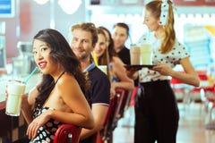 Folk i amerikansk matställe eller restaurang med milkshakar Arkivbild