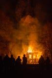 Folk i bakgrunden av ett brinnande hus Arkivbild
