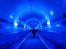 Folk i den blåa upplysta Elbtunnelen, i Hamburg, Tyskland Arkivbilder
