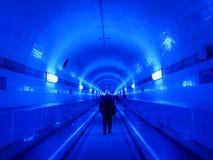 Folk i den blåa upplysta Elbtunnelen, i Hamburg, Tyskland Royaltyfri Bild
