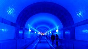 Folk i den blåa upplysta Elbtunnelen, i Hamburg, Tyskland Arkivbild