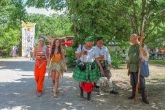Folk i dräkt - två härliga kvinnor i sexiga dräkter och par i kiltar och man i medeltida kläder på Renassiance festival M Arkivfoto