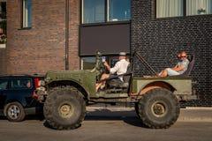 Folk i en öppen offroad bil med jätte- gummihjul Arkivfoto